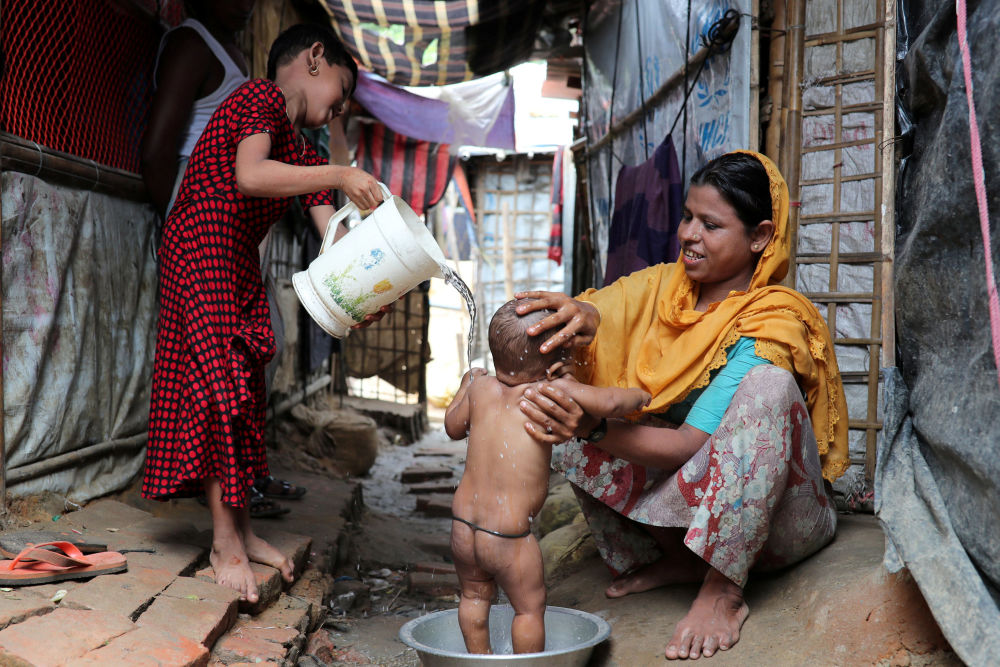 Mulher rohingya lava seu filho no campo de refugiados de Kutupalong, em Bangladesh