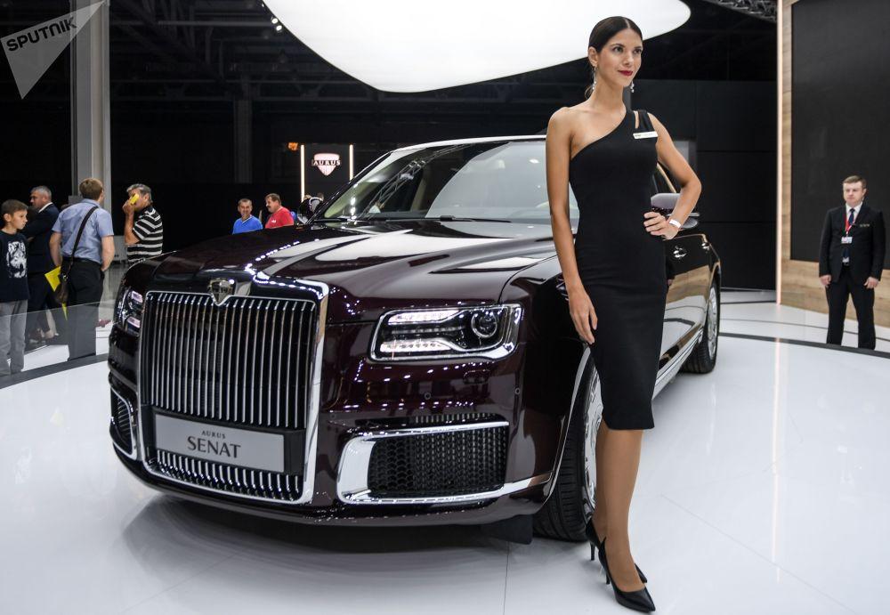 Modelo posa ao lado da limusine russa Aurus Senat no Salão do Automóvel de Moscou 2018