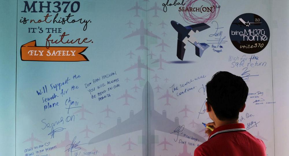 Um homen escreve condolências no Dia da Memória dos trágicos acontecimentos com o avião MH370