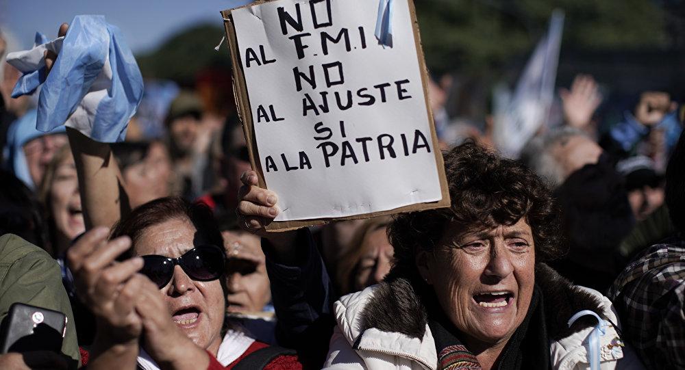 Mulheres gritam contra o presidente argentino Mauricio Macri. Uma delas, no centro, segura uma placa com a mensagem Não ao FMI, não à austeridade, sim à pátria-mãe, em Buenos Aires. Milhares protestaram contra a decisão do governo de pedir socorro ao FMI. Foto de 25 de maio de 2018.