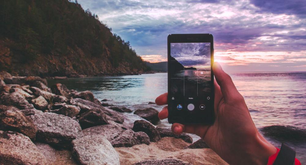 Celular tira foto da magnífica paisagem do lago Baikal (sul da Sibéria), através do qual é possivel ver o pôr do sol e parte da montanha (imagem referencial)