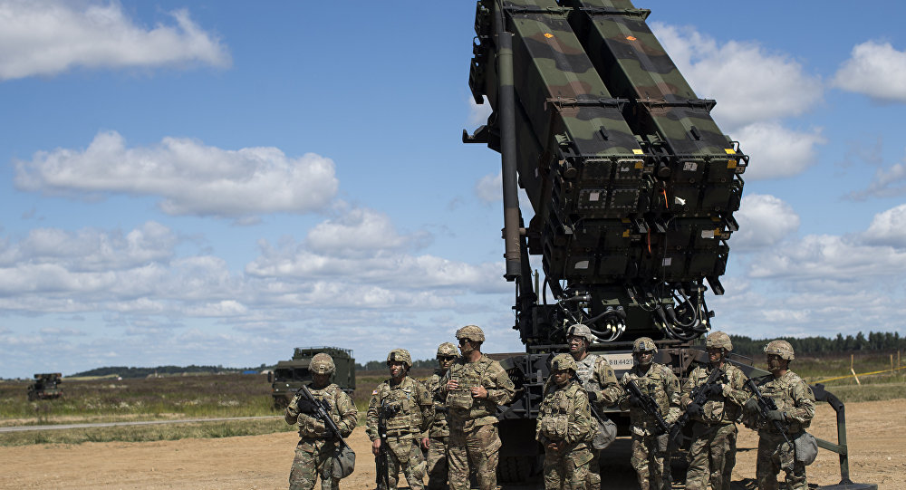 Membros do Exército do 10º Comando do Exército para Ar e Defesa Aérea ao lado de sistema de defesa de antiaérea durante exercício multinacional de unidades de defesa na base aérea de Siauliai, na Lituânia.