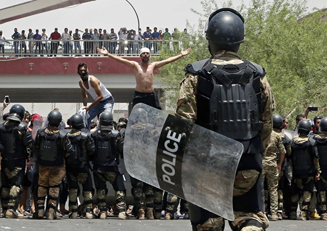 Police prevent protesters from storming the provincial council building during a demonstration in Basra, Iraq, 340 miles (550 kilometers) southeast of Baghdad, on Sunday, July 15, 2018