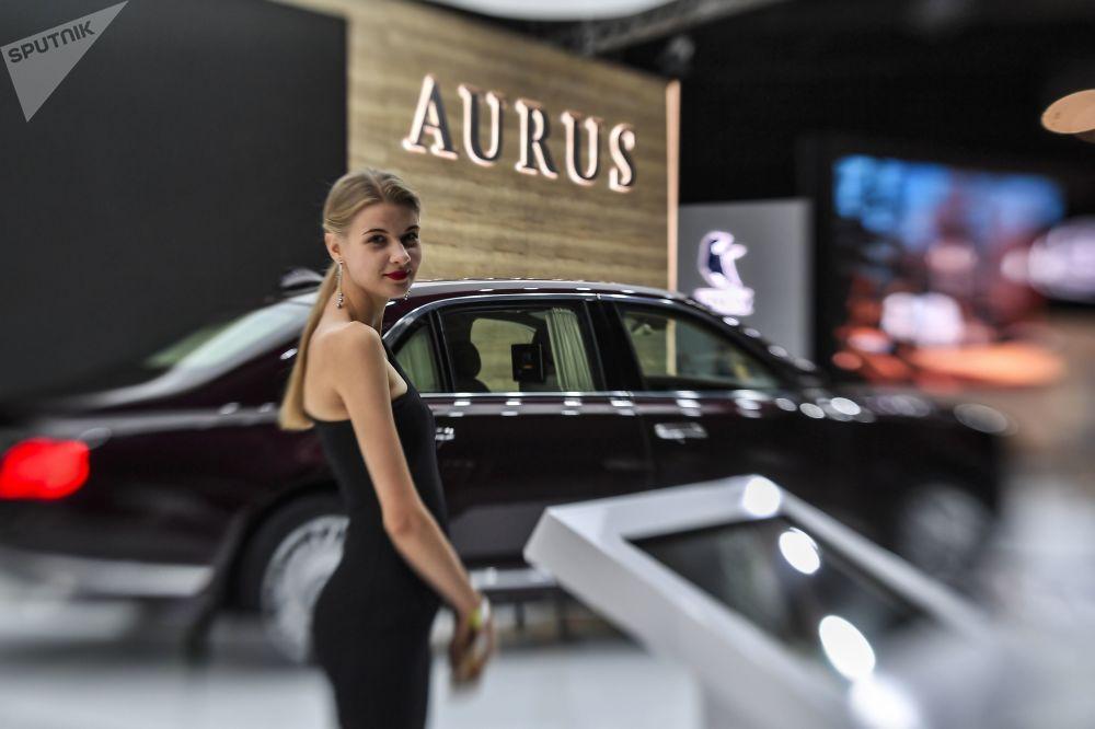 Jovem perto do veículo Aurus Senat no Salão Internacional do Automóvel de Moscou 2018