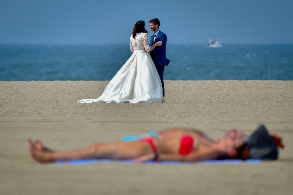 Casal de noivos ao fundo, enquanto pessoas tomam sol na praia em Deauville, França