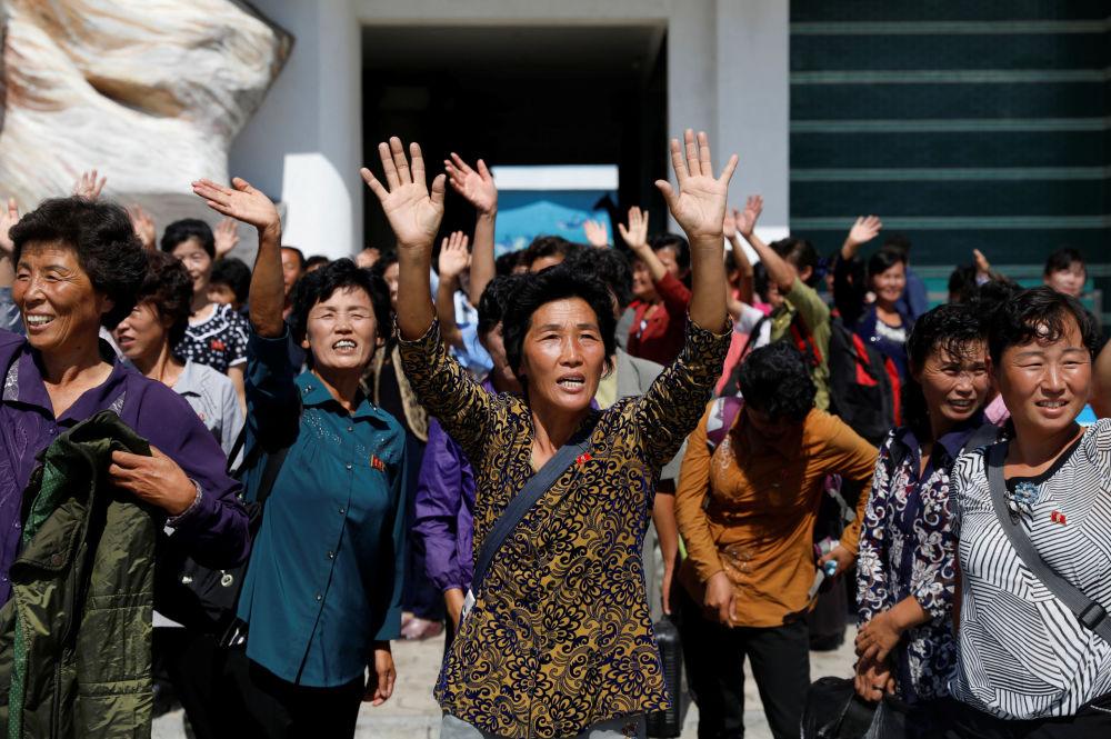 Civis acenam para militares norte-coreanos perto do Museu de História Natural em Pyongyang