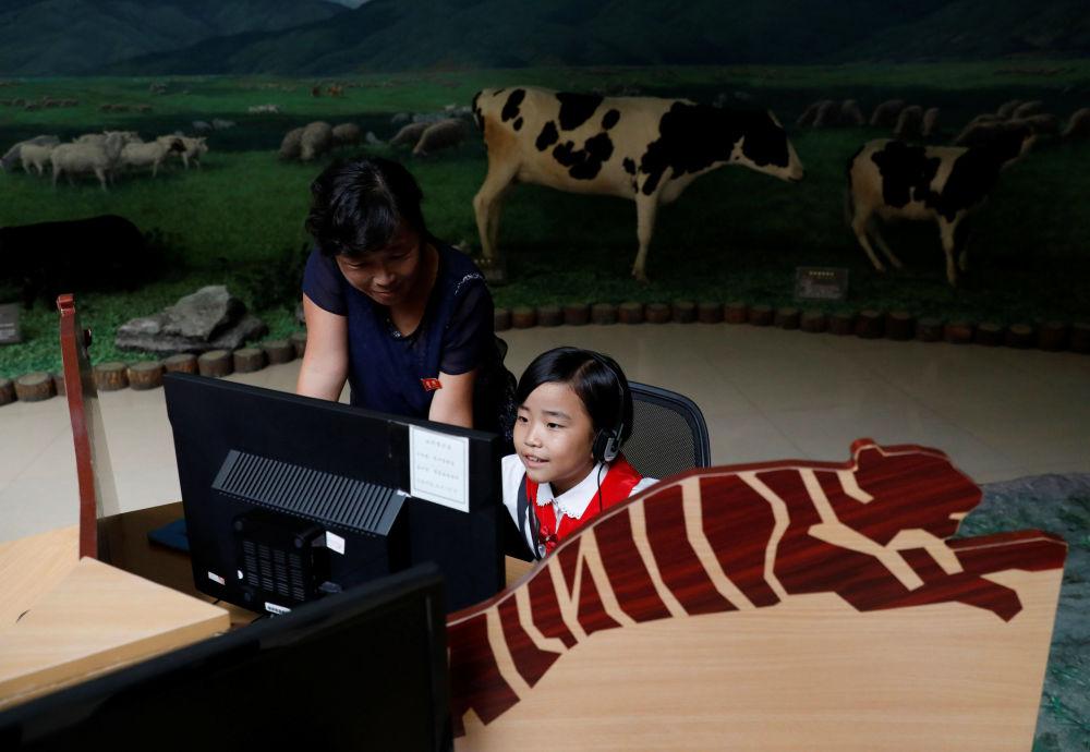 Uma menina ouve informação em um computador no Museu de História Natural em Pyongyang