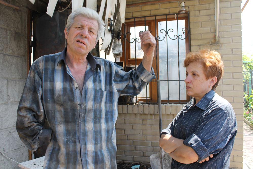 Moradores de Donetsk mostram sua casa destruída por bombardeio das Forças Armadas ucranianas