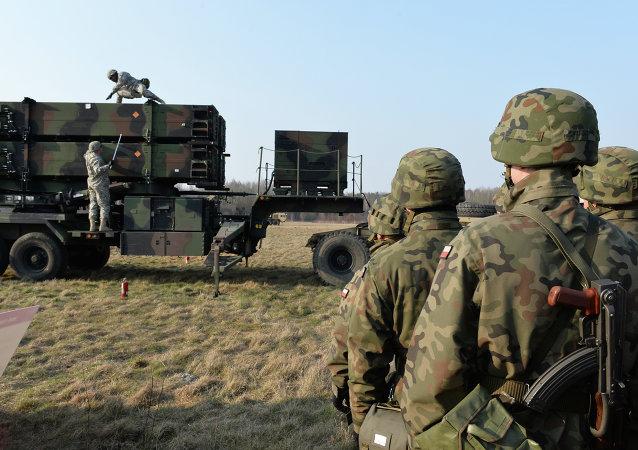 Soldados poloneses observam militares americanos operando um sistema antimísseis Patriot, em Sochaczew, Polônia