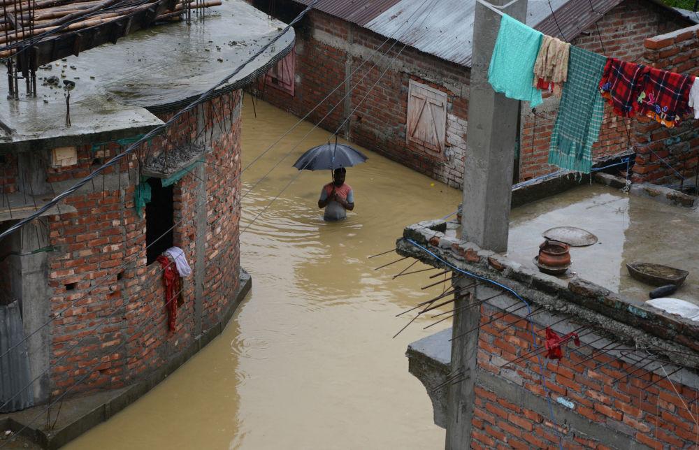 Homem no meio de uma rua inundada na cidade indiana de Siliguri, em 10 de setembro de 2018