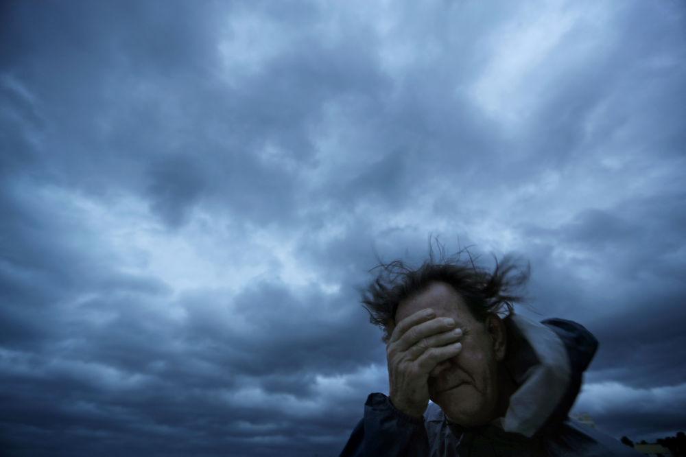 Homem tapando o rosto do vento e areia durante o furacão Florence em Myrtle Beach, Carolina do Sul