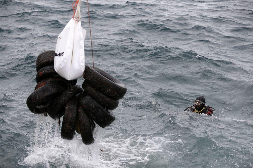 Tripulação de um navio levanta pneus de carros do mar perto da costa de Ática