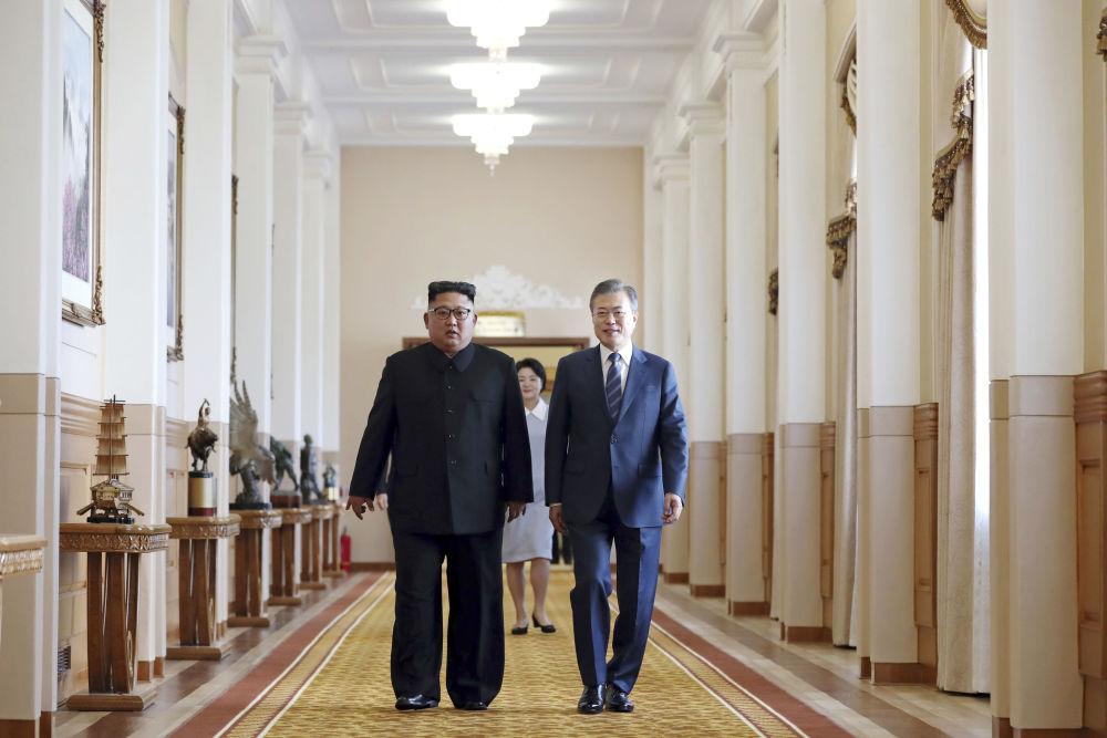 Presidente norte-coreano Kim Jong-un (esquerda) e líder sul-coreano Moon Jae-in (direita) andam juntos para assinar acordo conjunto, na capital norte-coreana de Pyongyang