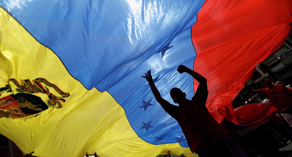 Apoiadores pró-governo segurando a bandeira da Venezuela em protesto contra o presidente dos EUA, Donald Trump, em Caracas, 14 de agosto de 2017