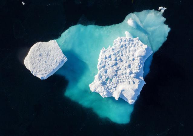 Iceberg flutua em um fiorde (golfo encurvado e profundo que se situa entre montanhas muito altas e íngremes) perto da cidade de Tasiilaq, no sudeste da Groenlândia, em 19 de junho de 2018