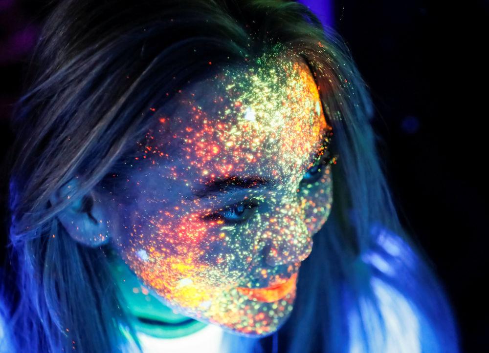 Participante da corrida Yarkokross na cidade de Almaty, no Cazaquistão, aparece com rosto pintado de cores fluorescentes