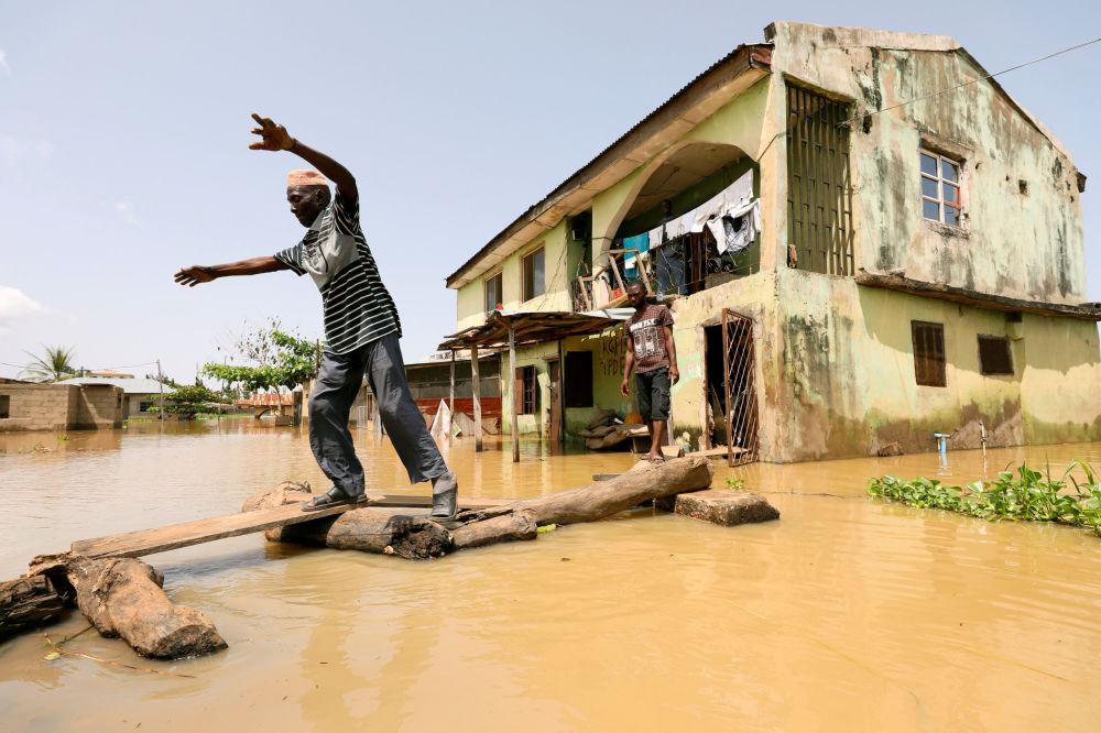Habitante do estado nigeriano de Kogi anda pela rua em meio a uma inundação