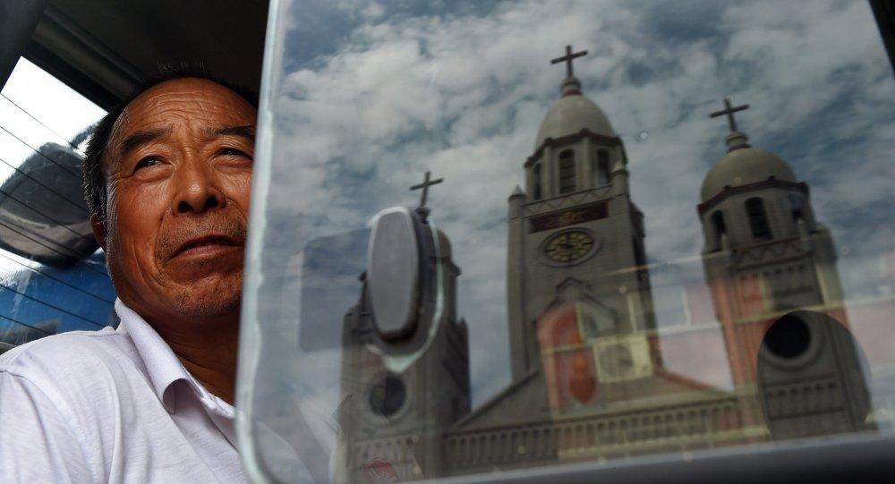 A Igreja Católica do Sagrado Coração de Jesus é vista refletida em uma janela enquanto um homem observa o monumento de uma van.