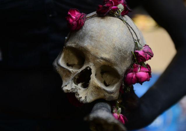 Homem segura caveira com rosas nas mãos durante ritual religioso em Allahabad, na Índia (imagem de arquivo)
