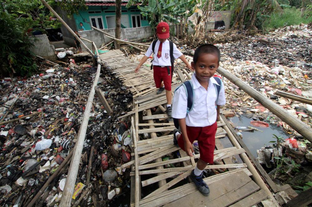 Alunos atravessando uma ponte de bambu por cima do rio Ciliwung cheio de lixo, Indonésia.