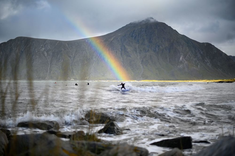 Surfista com arco-íris em fundo no norte da Noruega.