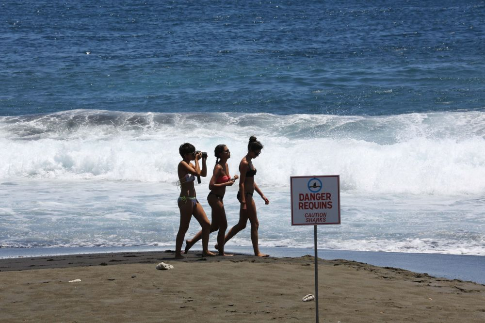 Praia na ilha de Reunião, Oceano Índico. Esta ilha também tem fama de uma das capitais dos tubarões. Em 1999, as autoridades locais proibiram matar estes animais, o que contribuiu para um crescimento elevado de sua população.