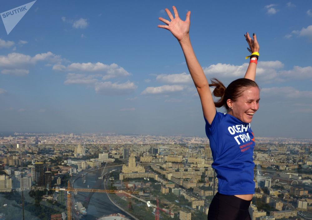 Participante de uma corrida festejando no topo de um arranha-céu no Centro Internacional de Negócios de Moscou
