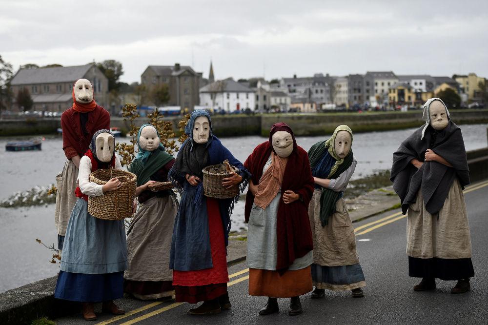 Atores do grupo teatral Brú Theatre, representando a comunidade de pescadores datada de 100 anos atrás, se apresentam no cais da cidade islandesa de Galway