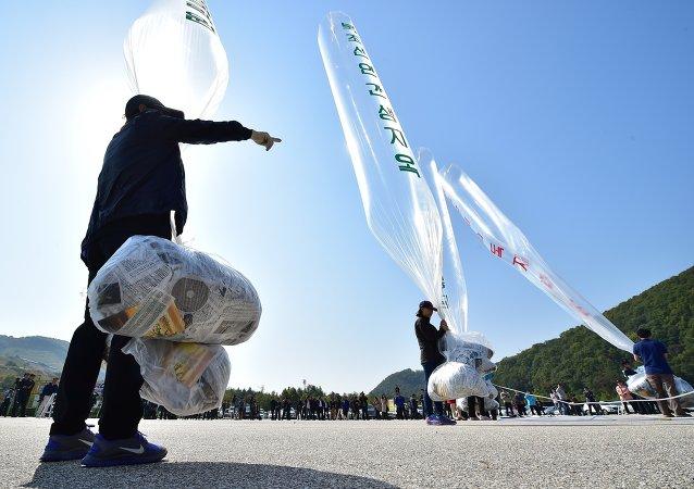 Ativistas sul-coreanos se preparam para soltar balões que transportam panfletos contra a Coreia do Norte em um parque perto da fronteira.