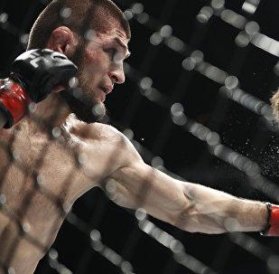 Khabib Nurmagomedov derruba Conor McGregor durante o combate pelo título de campeão peso-leve do UFC, 6 de outubro de 2018