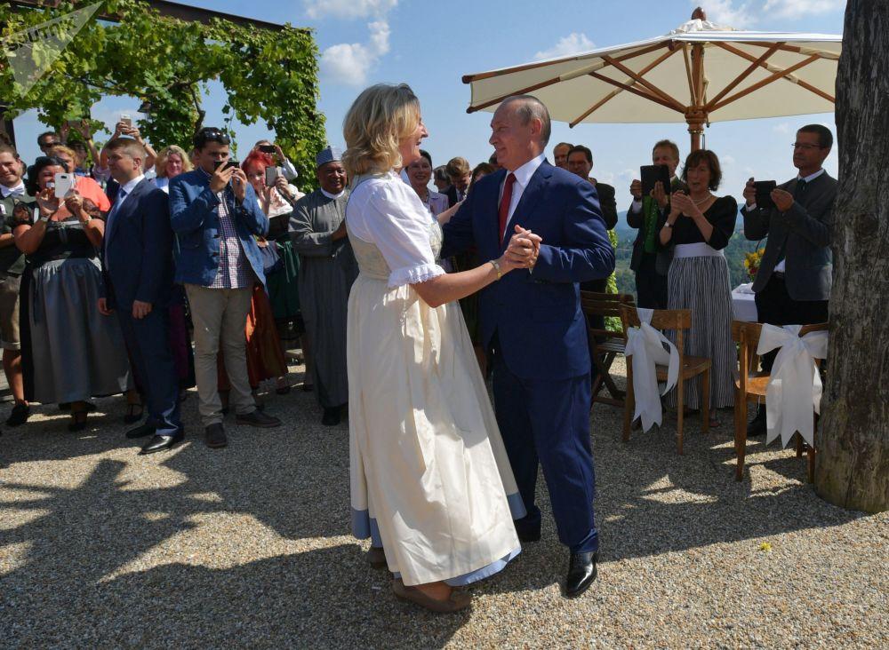 Vladimir Putin dança com a chanceler austríaca, Karin Kneissl, durante a cerimônia de casamento dela, 18 de agosto de 2018