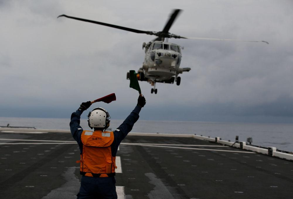 Tripulante do convés de voo do porta-helicópteros Kaga, Akiko Ihara, orienta um helicóptero a pousar no convés