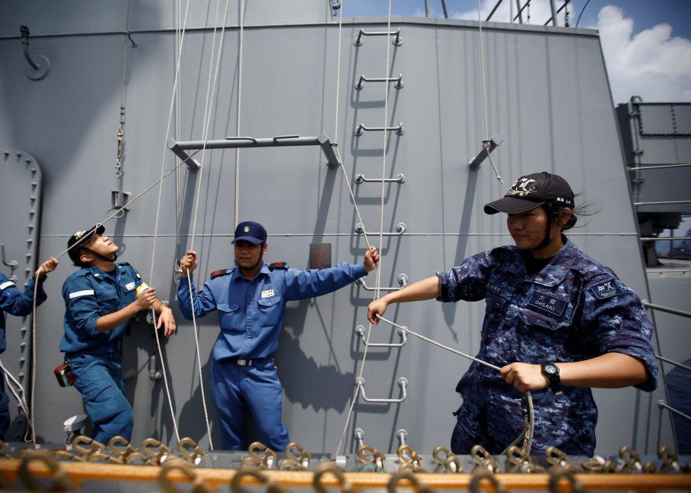Mulher marinheira pratica hasteamento de bandeiras de sinalização a bordo do porta-helicópteros Kaga no oceano Índico