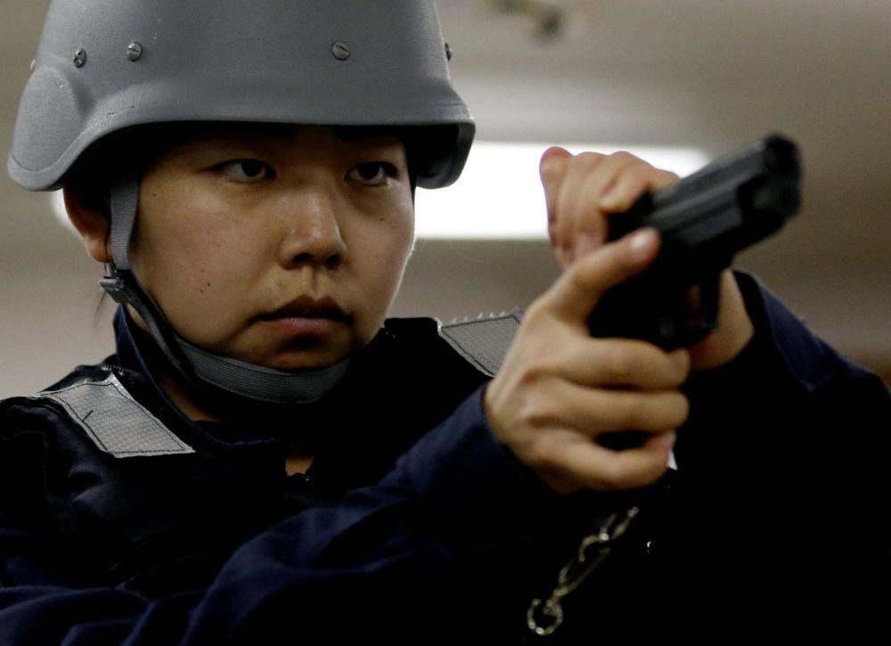 Membro da tripulação do navio japonês Kaga verifica sua pistola antes de treinamento a bordo do navio