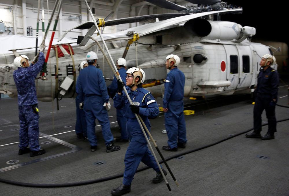 Membro da tripulação trabalha em um helicóptero SH-60K Sea Hawk no convés do hangar do navio japonês Kaga