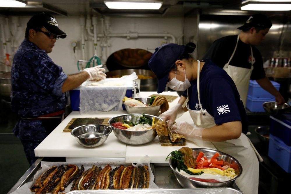 Cozinheira da tripulação do porta-helicópteros Kaga prepara comida a bordo do navio