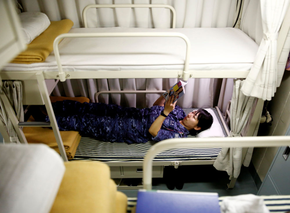 Membro da tripulação do porta-helicópteros japonês Kaga descansa em seu alojamento a bordo do navio
