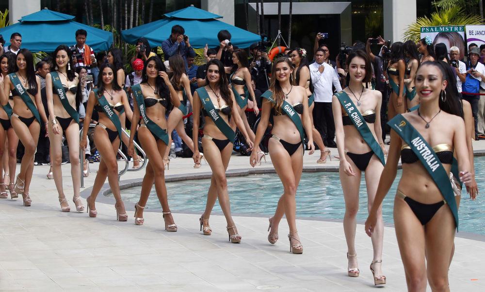 Representantes de vários países desfilam com traje de banho à beira da piscina durante o concurso Miss Terra 2018, nas Filipinas