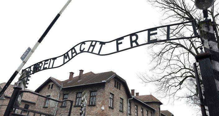Foto da placa Arbeit macht frei (Trabalho te torna livre) no portão principal do antigo campo de concentração e extermínio nazista alemão Auschwitz.