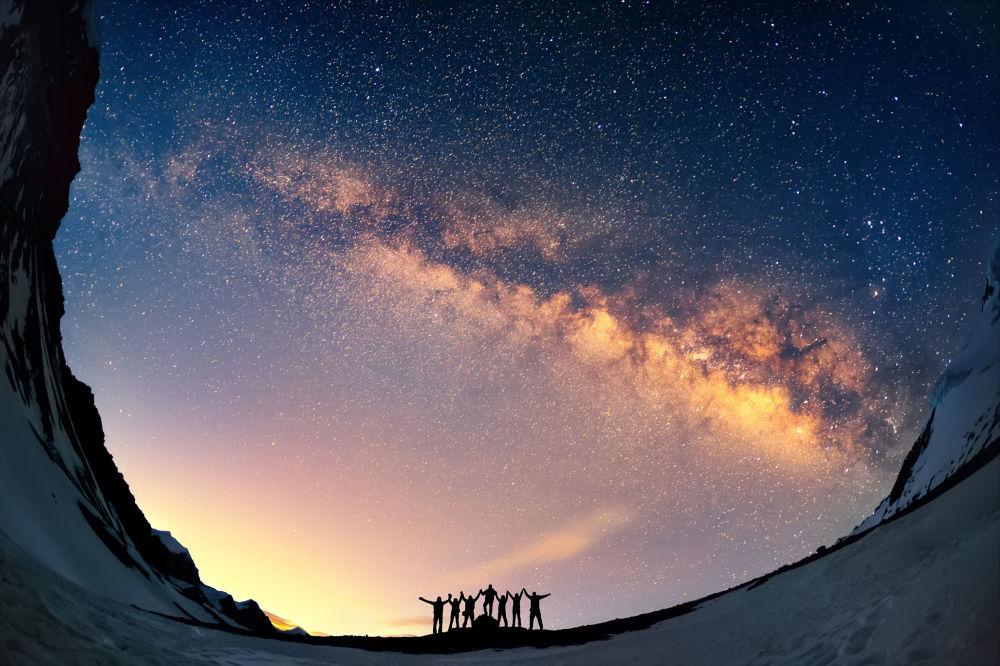 Turistas vistos de mãos dadas em meio à Via Láctea, nas montanhas nepalesas.