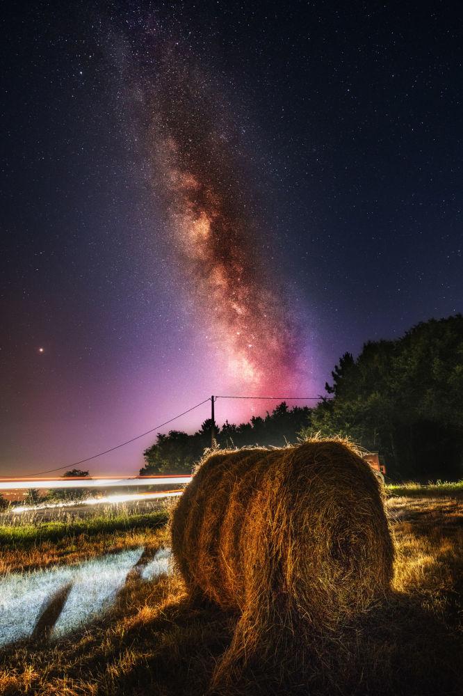 Via Láctea aparece no céu por cima de um campo de feno