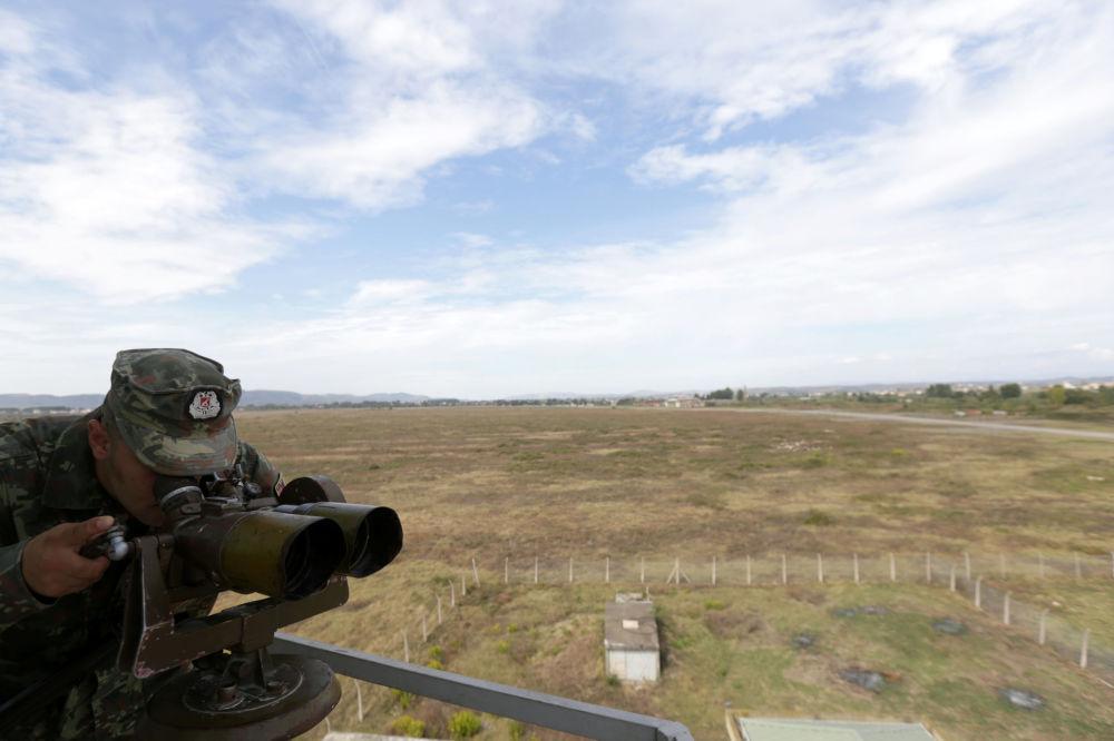 Militar da Força Aérea da Albânia utilizando binóculos na base aérea de Kucove