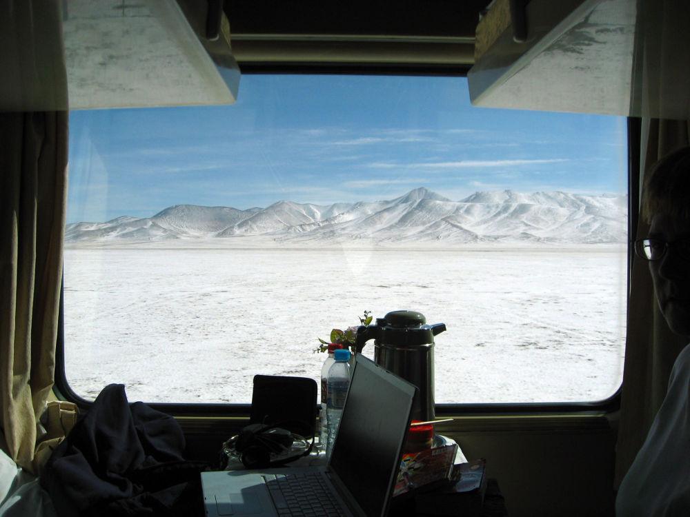 Imagem de dentro do vagão do trem, que liga Pequim (China) a Lhasa (Tibete), mostra montanhas cobertas por neve