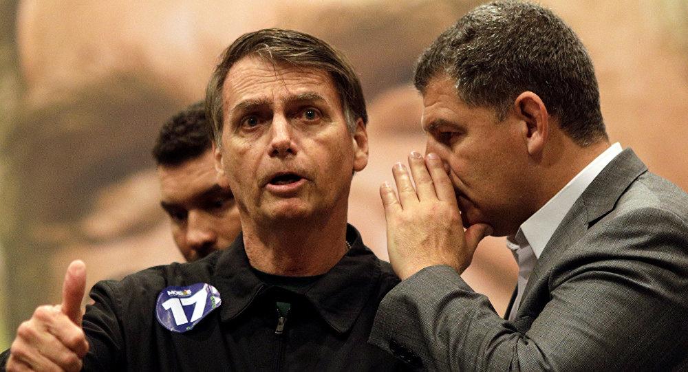 Gustavo Bebianno, presidente do partido PSL, fala a Jair Bolsonaro, candidato à presidencia do Brasil, durante uma coletiva no Rio, em 11 de outubro de 2018