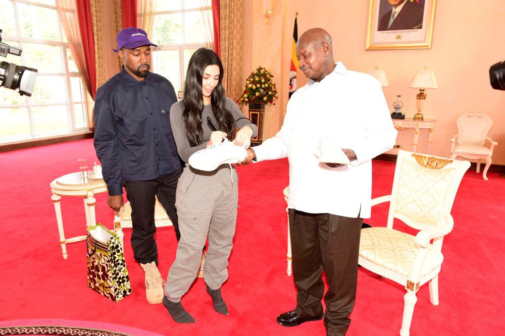 Rapper americano Kanye West observa sua esposa, Kim Kardashian, a autografar um tênis para o presidente ugandense, Yoweri Museveni, na sua residência, em 15 de outubro de 2018