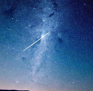 Meteoro atravessando céu noturno