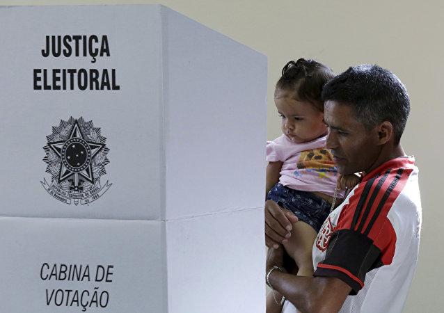 Homem com filha vota em um colégio no Brasil, em 28 de outubro de 2018