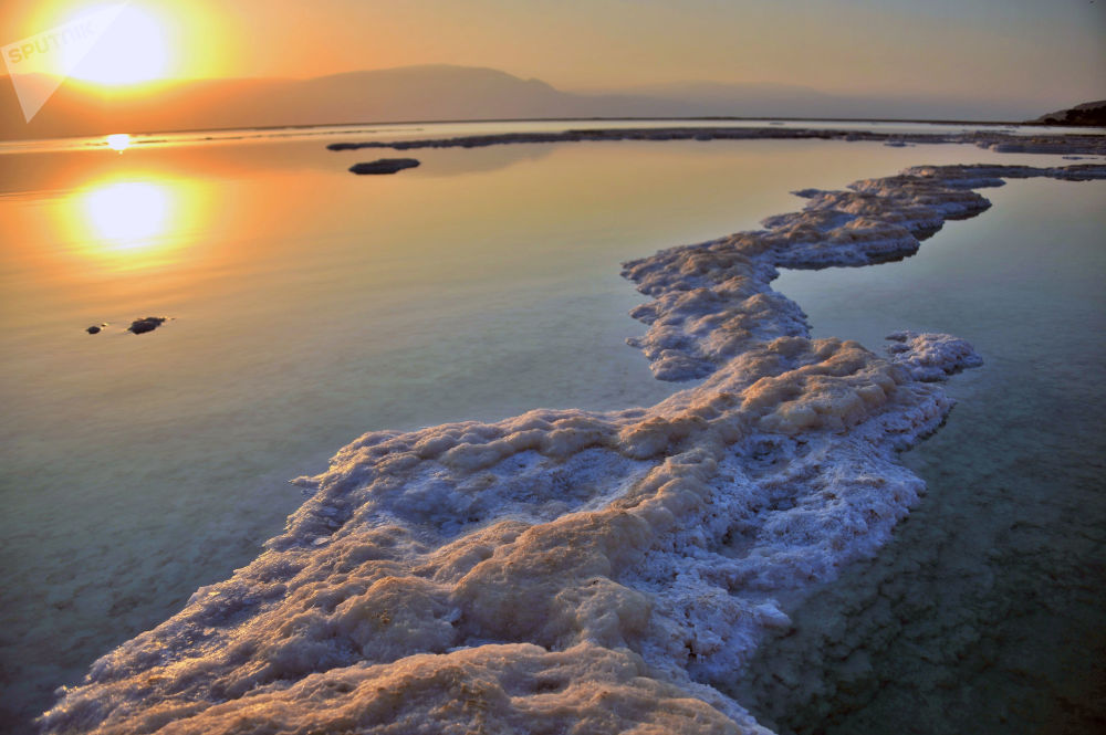 Vista para o mar Morto do lado do litoral israelense. O nível d'água cai com a velocidade de cerca 1 metro por ano devido ao processamento industrial de minerais e utilização de 80% de afluentes do lago