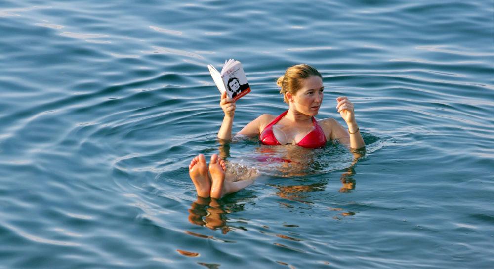 Moça lendo um livro enquanto relaxa na superfície d'água do mar Morto, Jordânia