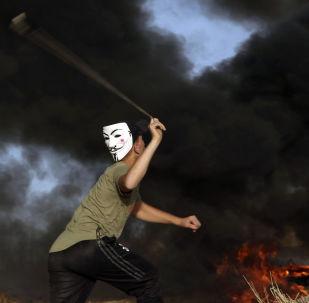 Manifestante usando máscara arremessa pedras contra as tropas israelenses perto da fronteira da Faixa de Gaza com Israel durante protesto, 29 de outubro de 2018
